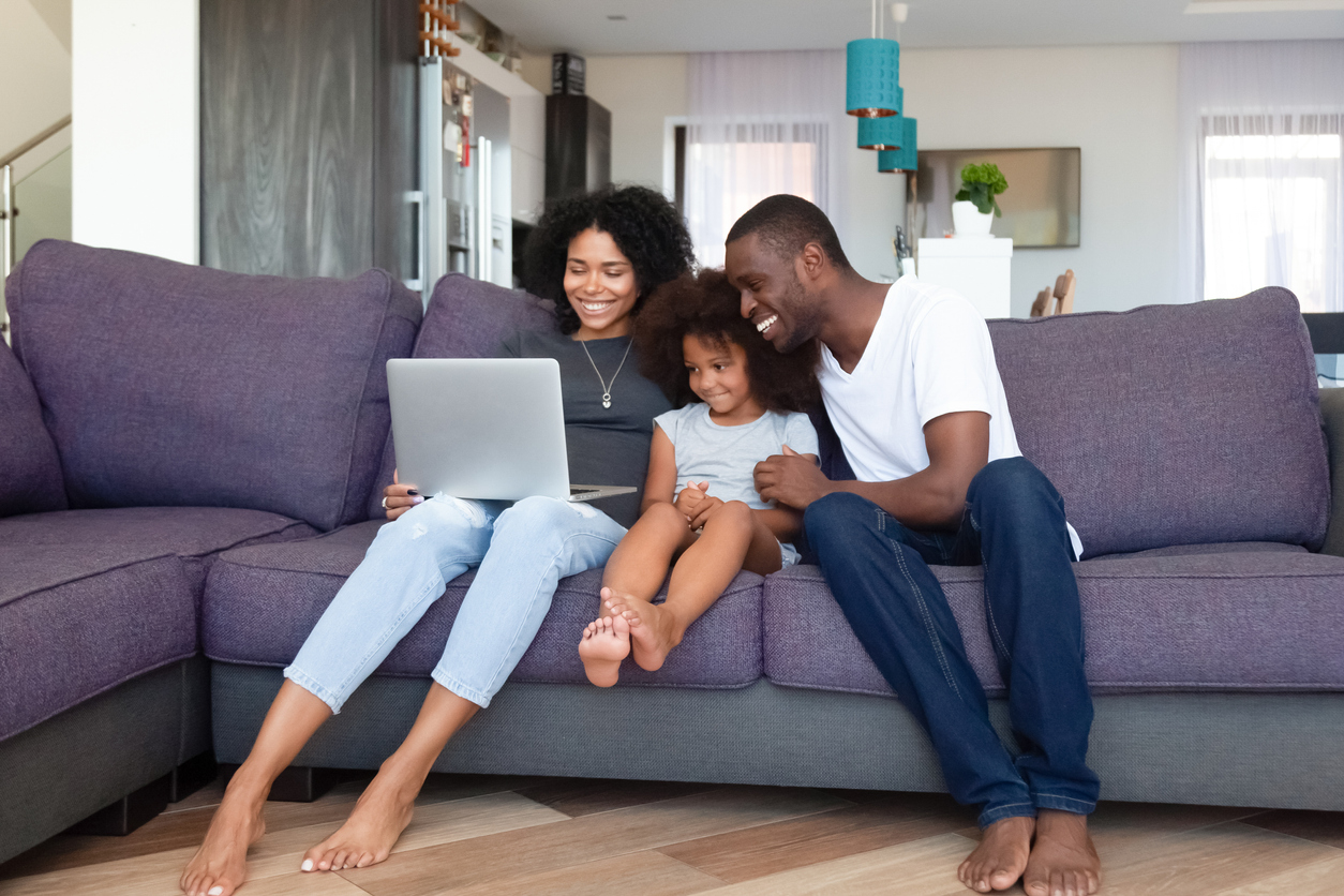 Family on couch looking at laptop.