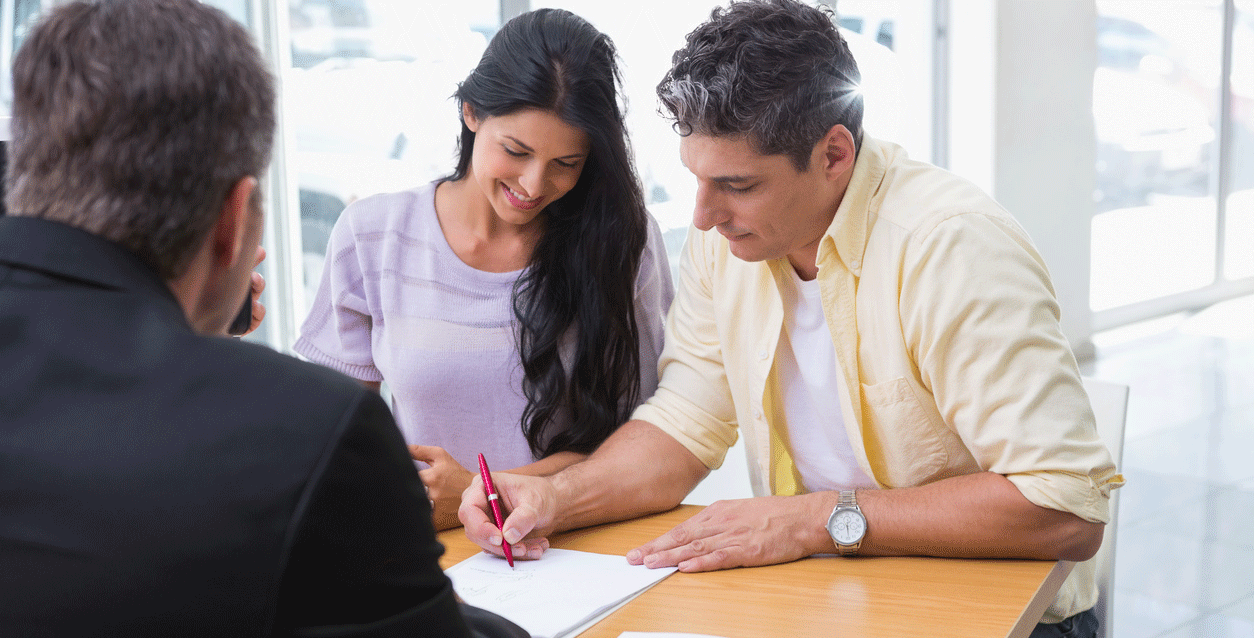 Couple in Dealership office, signing papers