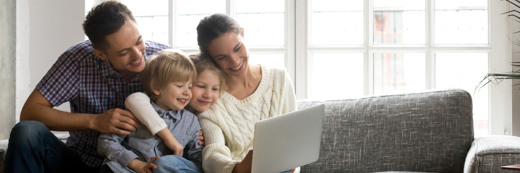 Family with two small children, smiling while gathered around a laptop.
