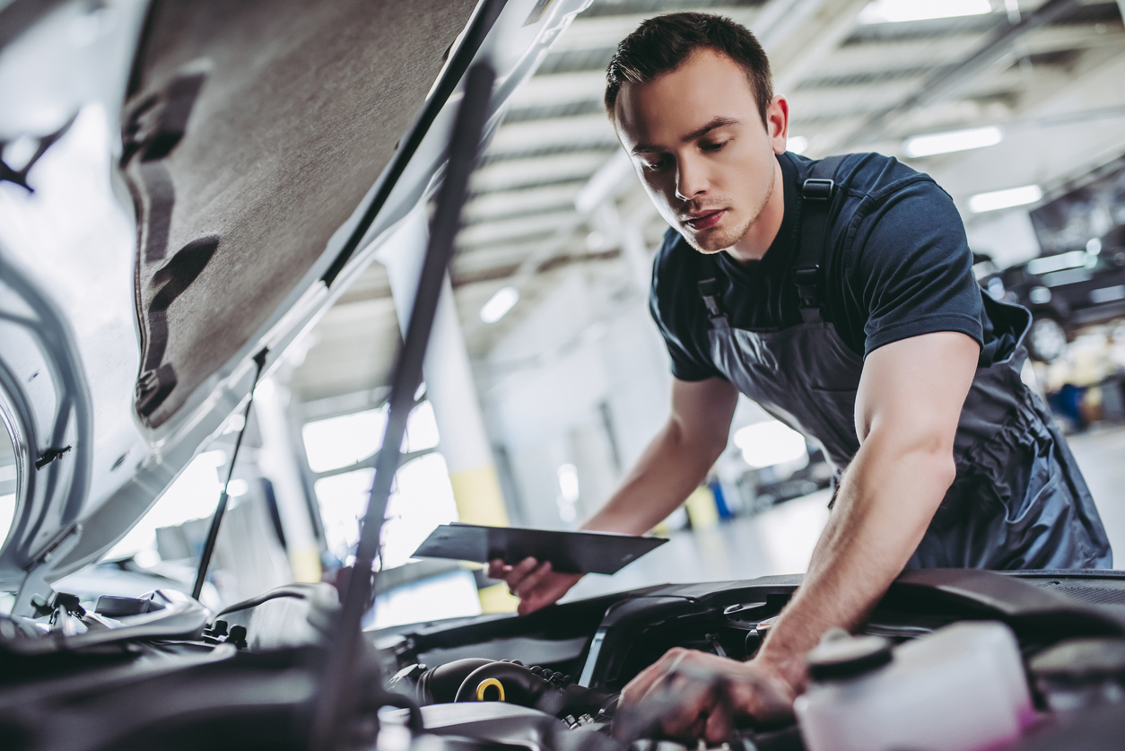 handsome auto service mechanic working on vehicle